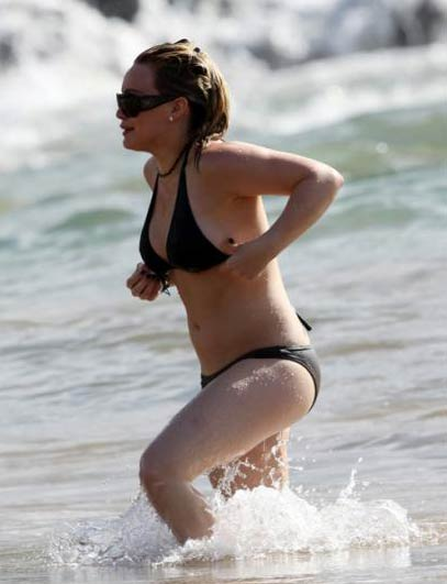 Hilary Duff fixes bikini top while on beach in Hawaii